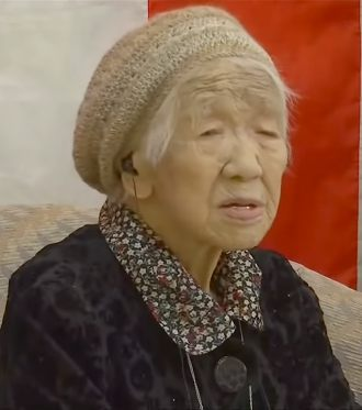 An image of Japan overlayed with a picture of a slim Japanese woman and Kane Tanaka from Fukuoka, Japan who is 116 years old.