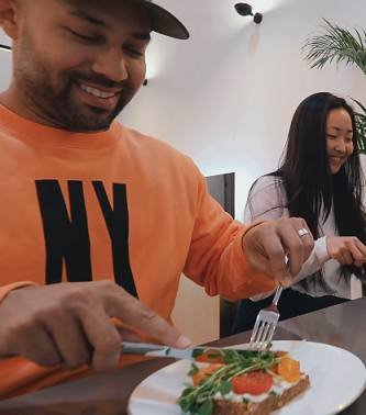 Kane samples Pia Muehlenbeck's meal made of Quark European style cottage cheese on Ezekiel bread with tomato, chives and sprouts.