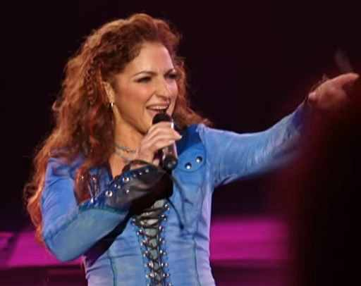 Gloria Estefan live in concert pointing to a fan